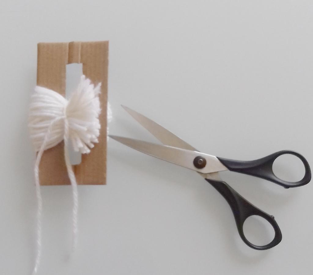 DIY, fait main : couper la laine avec ciseaux sur le fabricateur de pompons en carton, deco naturelle, slow living, Slow Déco