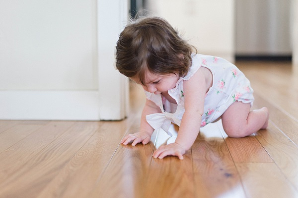 Bébé à quatre pattes sur un parquet en bois massif, non toxique, sans COV, dans une chambre de bébé saine, apaisante et écologique