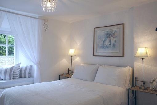 chambre intérieur blanc draps coton blanc, coussin taupe, lampes de chevet, tableau, lumière tamisée, fenêtre sur jardin, lustre, oreillers, ménage, santé, deco naturelle, slow design