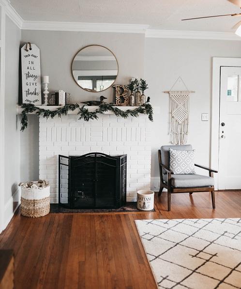 Salon blanc, cheminée avec insert, fauteuil, tapis, porte, miroir, déco Noël, parquet bois brut, intérieur sain et naturel, déco écologique, astuces, bienfaits santé ménage hiver, slow design, slow living